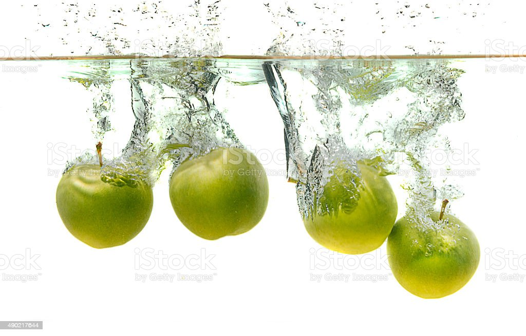 Green apples splashing into water on isolated white background stock photo