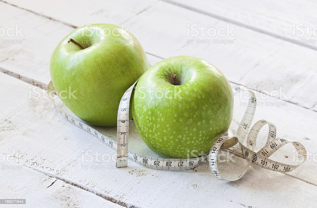 Green apples with measuring tape on wooden table stock photo