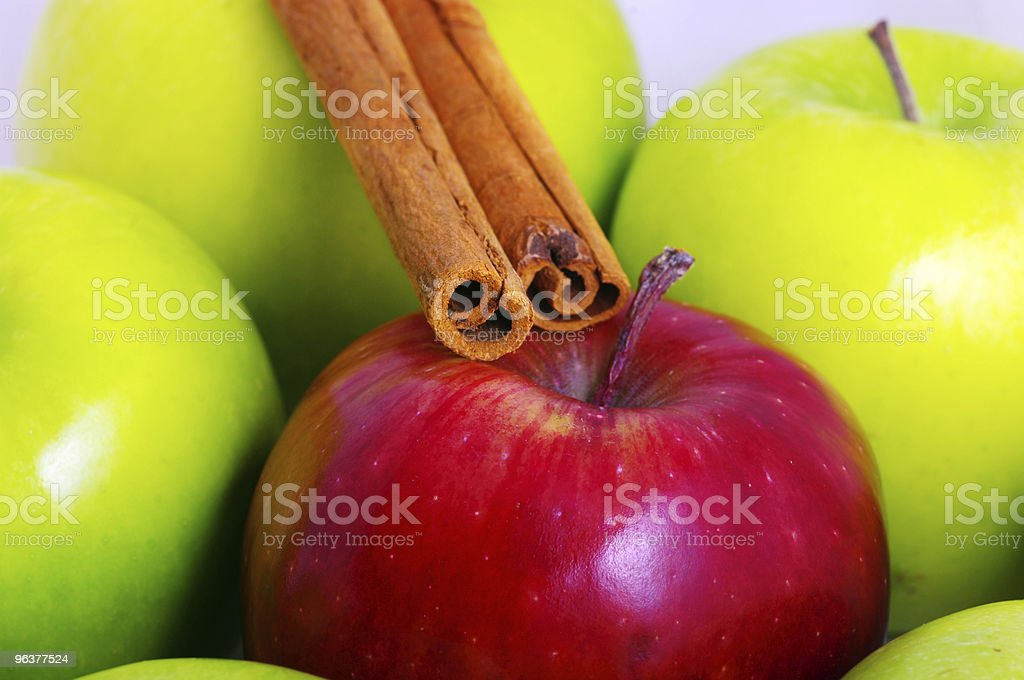 green apples with one red apple and cinnamon stick. royalty-free stock photo