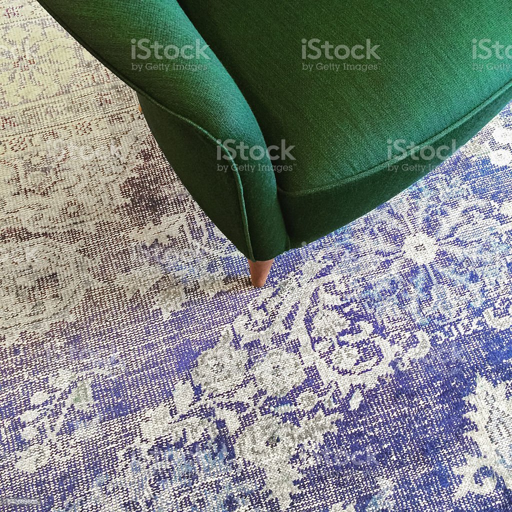 Green armchair on blue retro style carpet stock photo