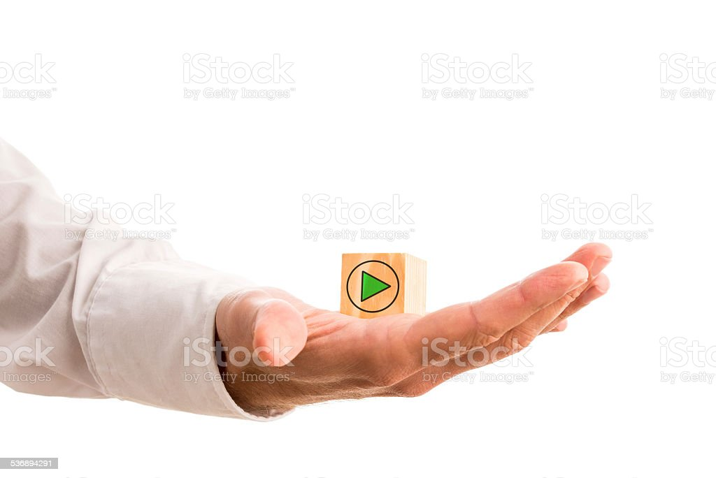 Green arrow on a wooden cube in a mans hand stock photo