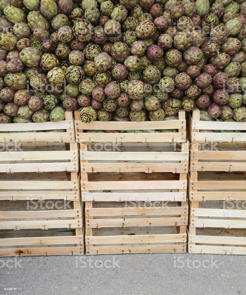 green artichokes and boxes for sale at the grocery store stock photo