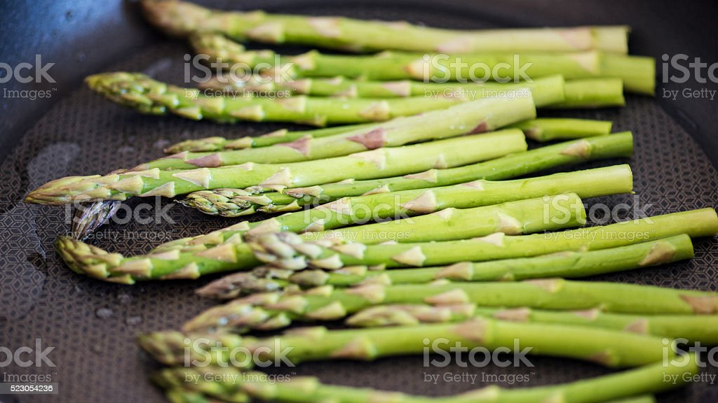 Green asparagus being fried for dinner stock photo