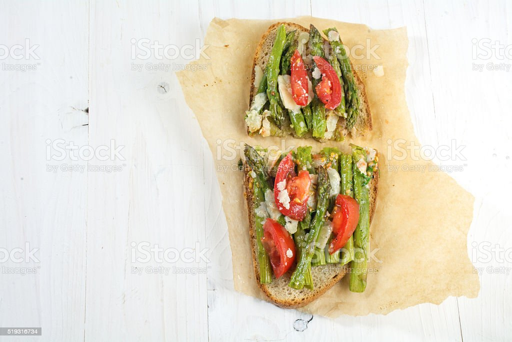 green asparagus, tomatoes and parmesan gratinated on bread, from above stock photo