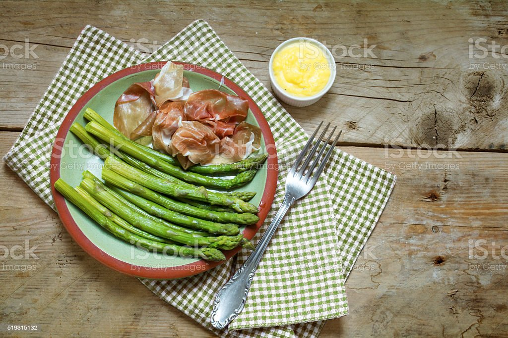 green asparagus with gammon on an earthenware plate, rustic wood stock photo