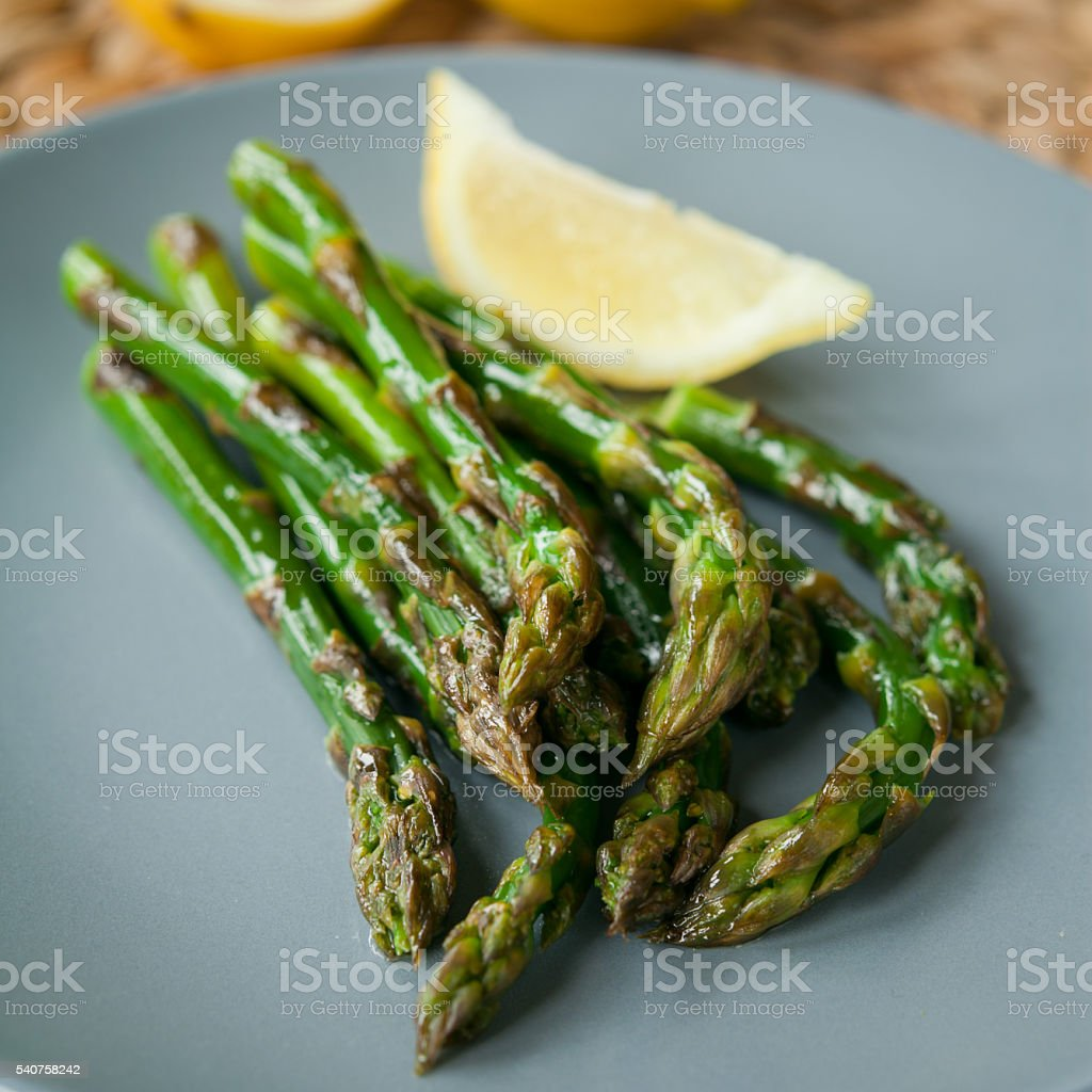 Green asparagus with lemon juice. stock photo