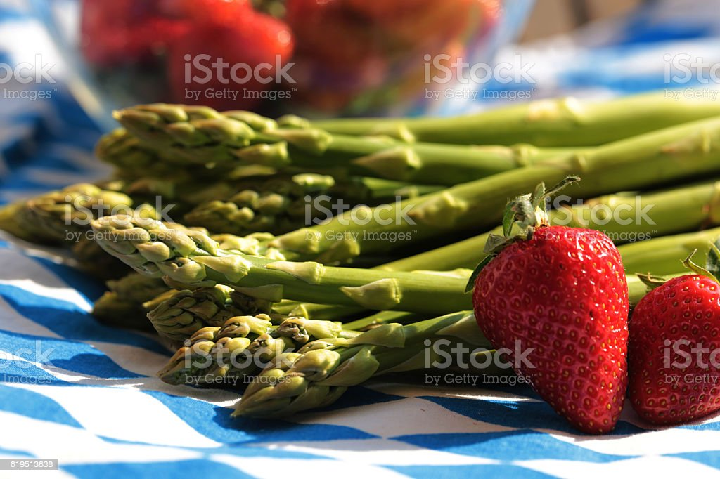 green asparagus with strawberries , on blue white bavarian colors stock photo