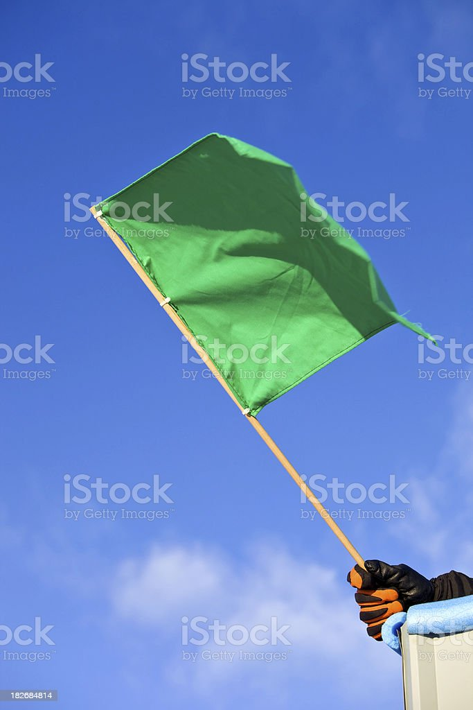 Green Auto Race Flag against a Clear Blue Sky stock photo