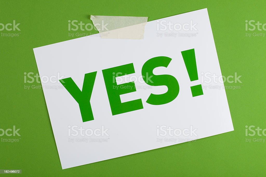 Green background with taped sign reading YES  royalty-free stock photo