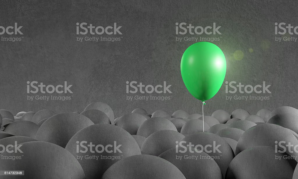 Green balloon rising from gray background: individuality, standing out stock photo