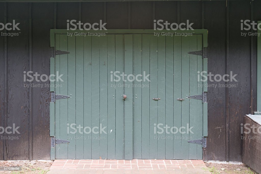 Green Barn Doors on Black Wall stock photo
