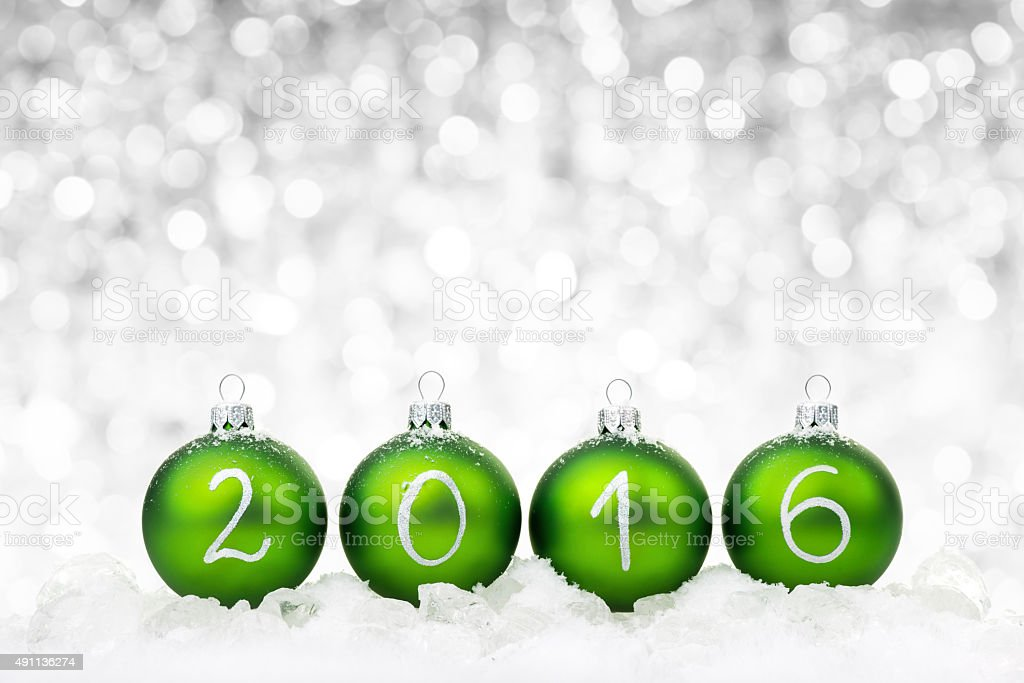 Green baubles 2016 on ice stock photo