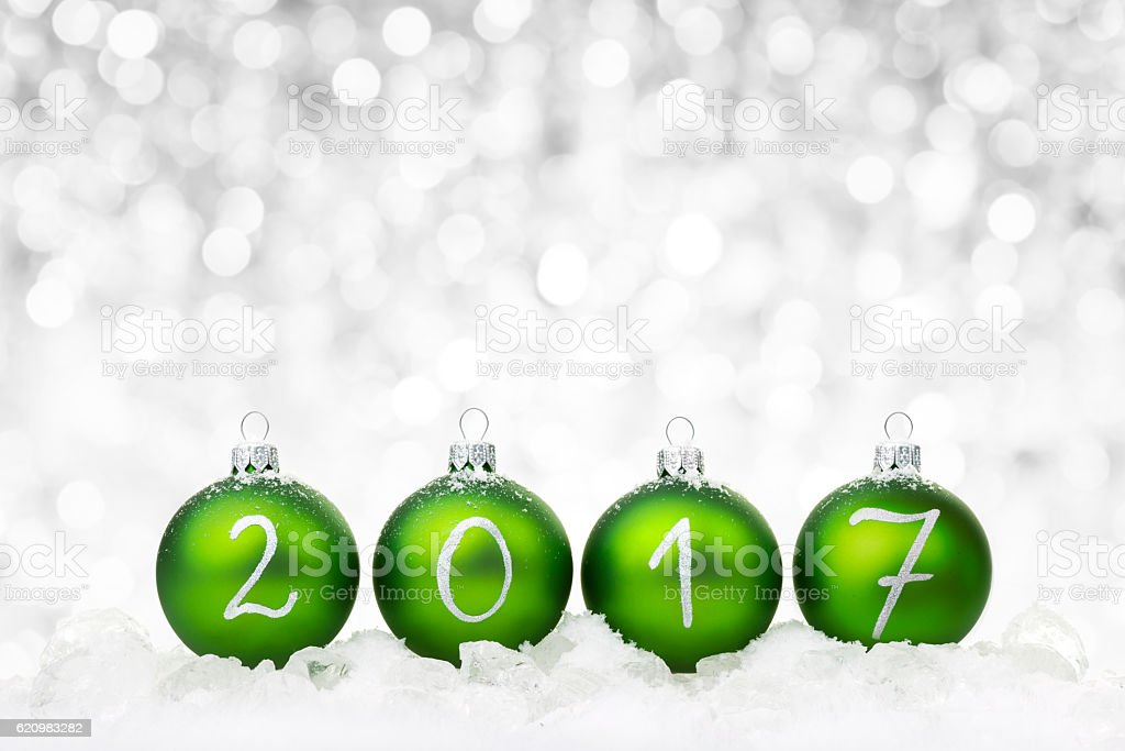 Green baubles 2017 on ice stock photo