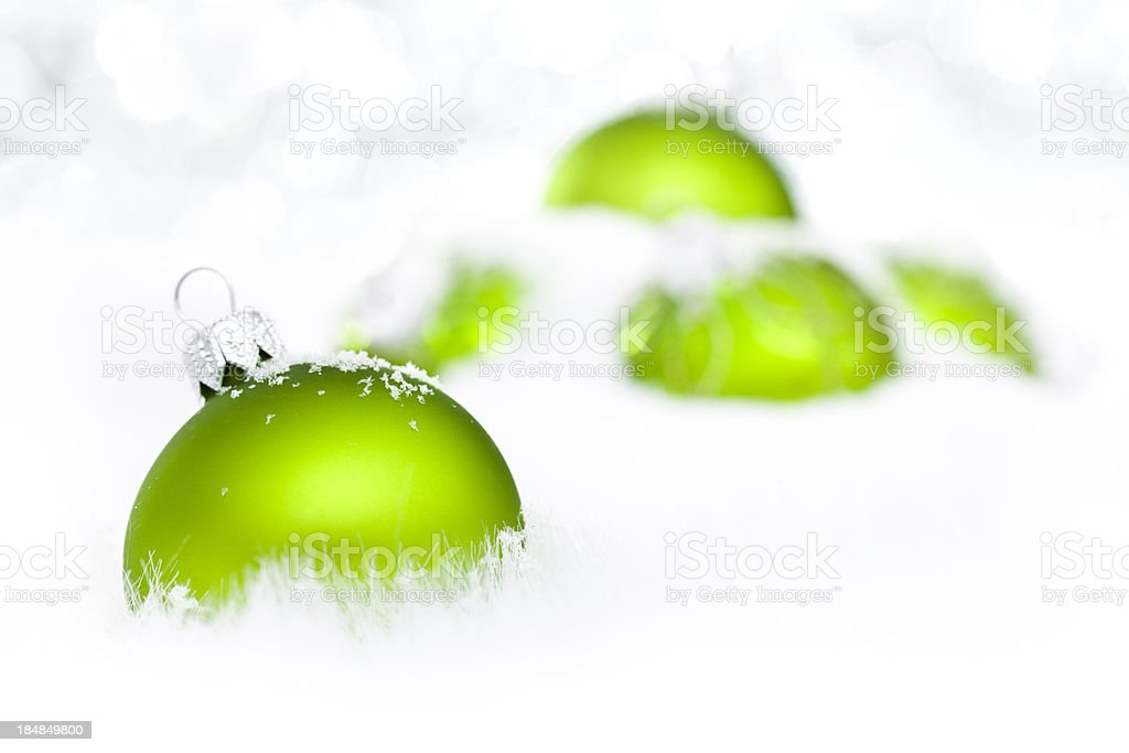 Green Baubles on snow stock photo