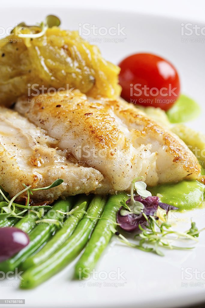 Green beans, olives and tomato accompany restaurant grilled fish stock photo