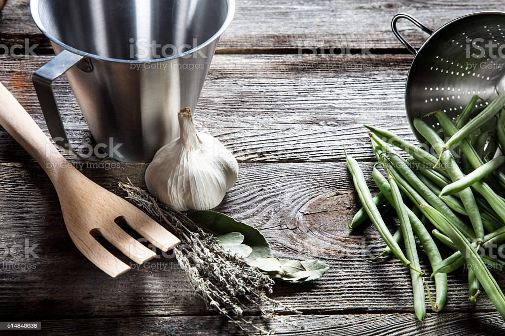 green beans with stainless steel utensils on retro wood background stock photo