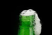 Green beer bottle neck with foam on black
