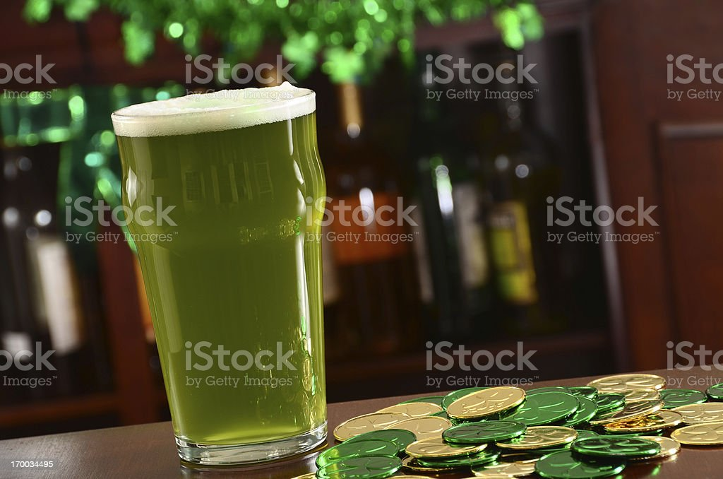 Green beer with green and gold coins on bar stock photo