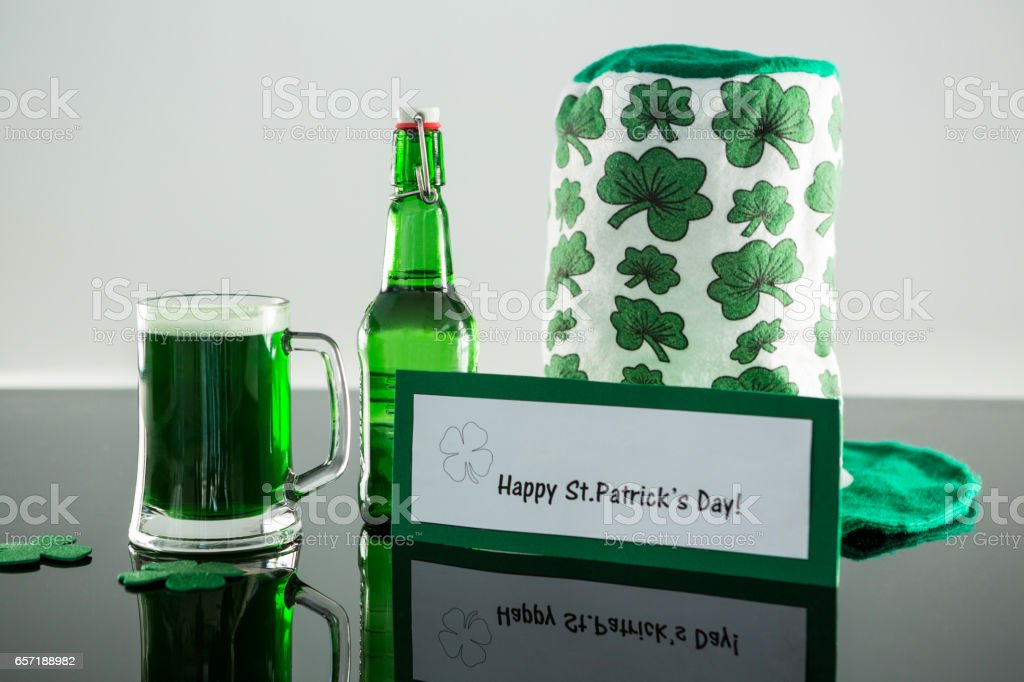 Green beer with shamrock, leprechaun hat and placard of St Patricks Day stock photo