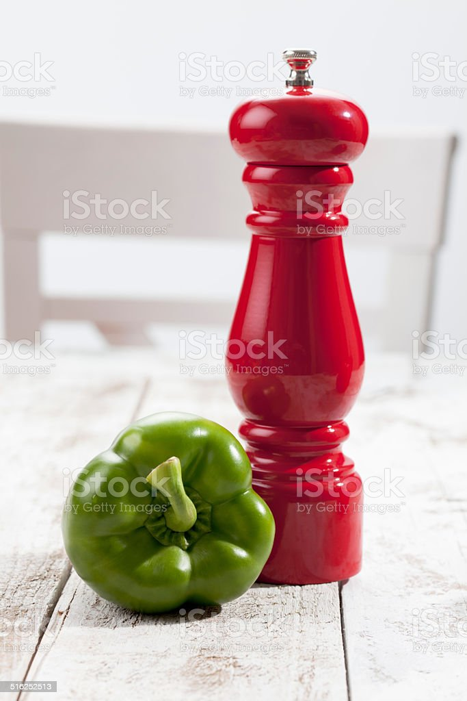 Green bell pepper, red pepper grinder on white wooden table stock photo