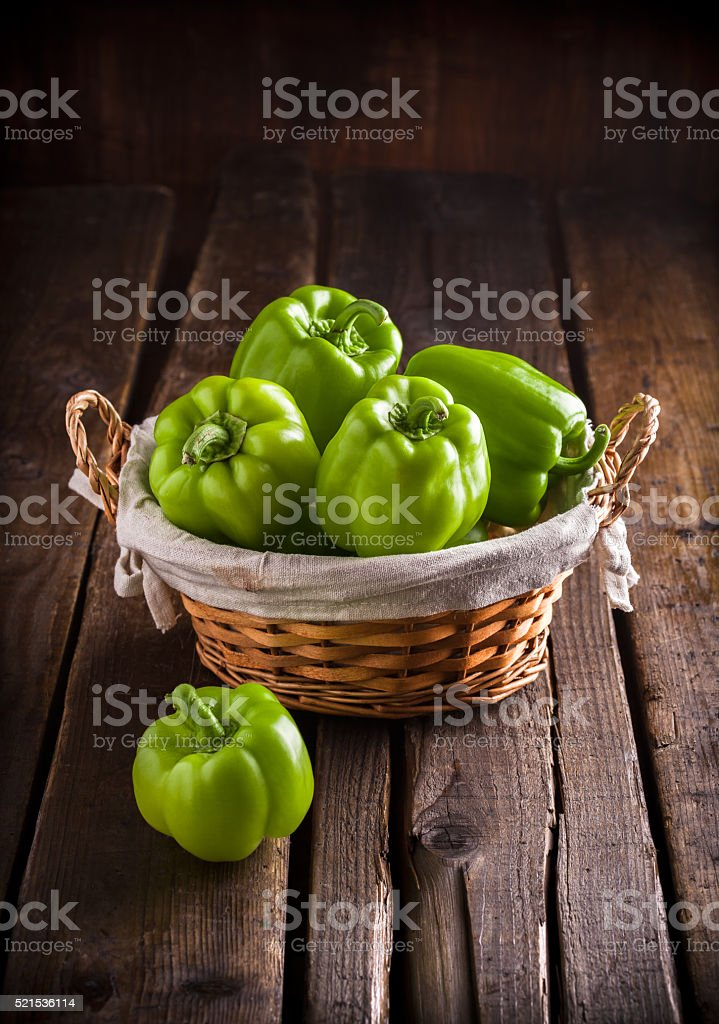 Green bell peppers in wicker basket on dark background stock photo