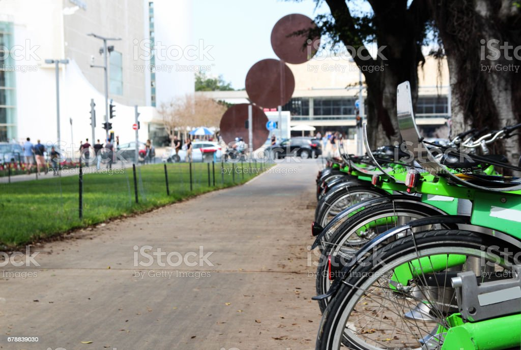 Green bikes for rent on a central street on a sunny day stock photo