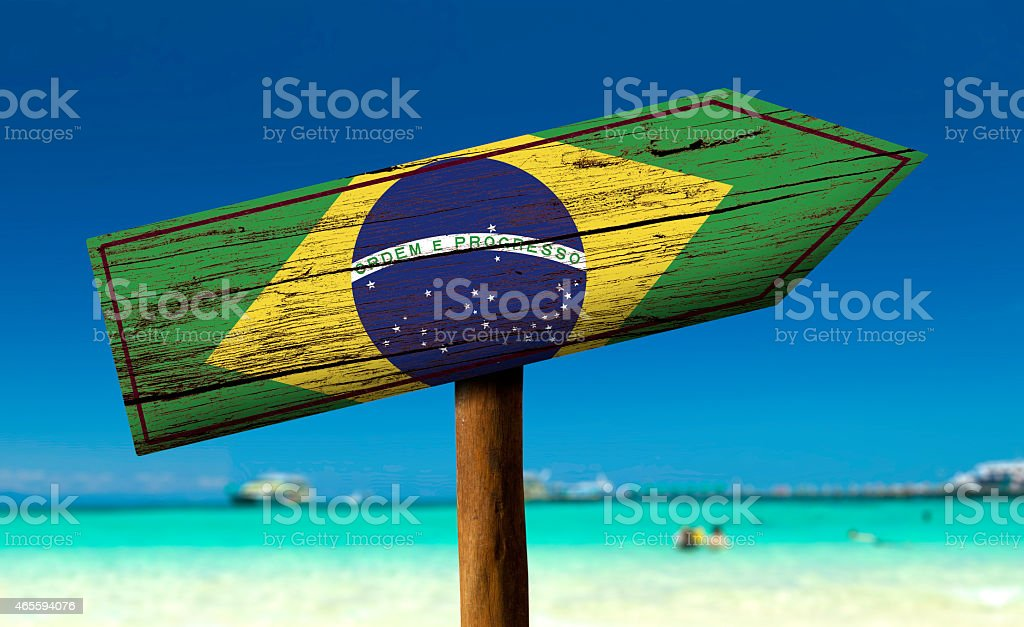 Green, blue and yellow sign on a beach in Brazil stock photo