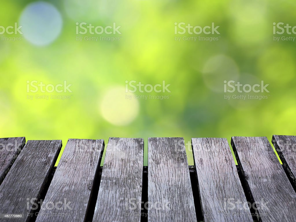Green blurred background and brown wooden floor. royalty-free stock photo