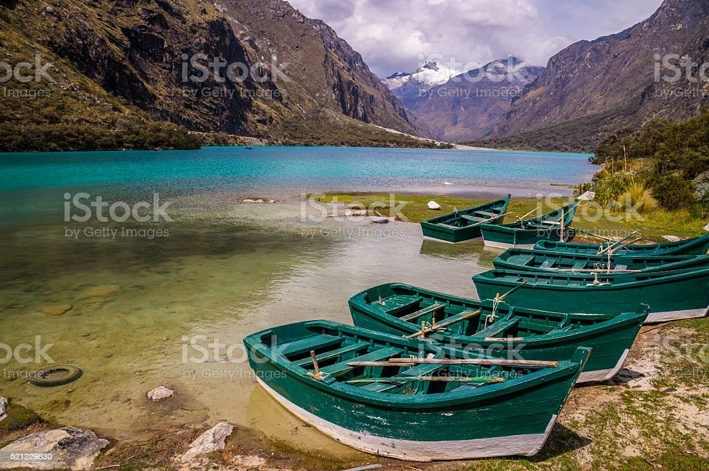 Green boats at glacier lagoon in Peruvian Andes stock photo
