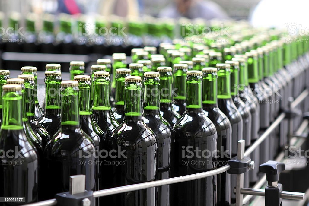 Green bottles being processed through a bottling plant stock photo