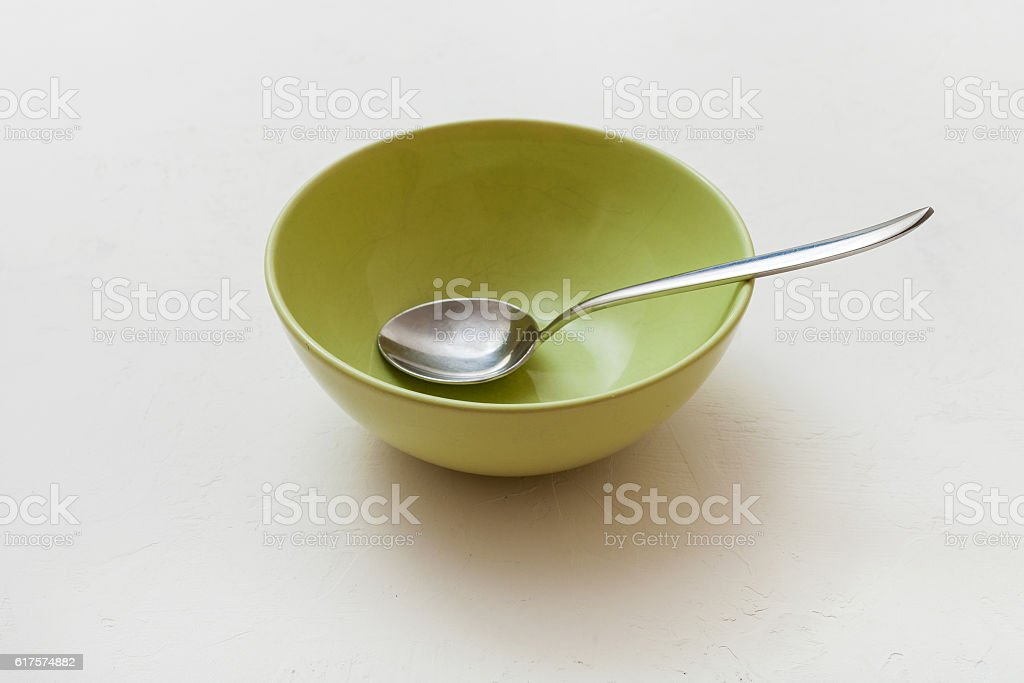 green bowl with spoon on white plaster stock photo