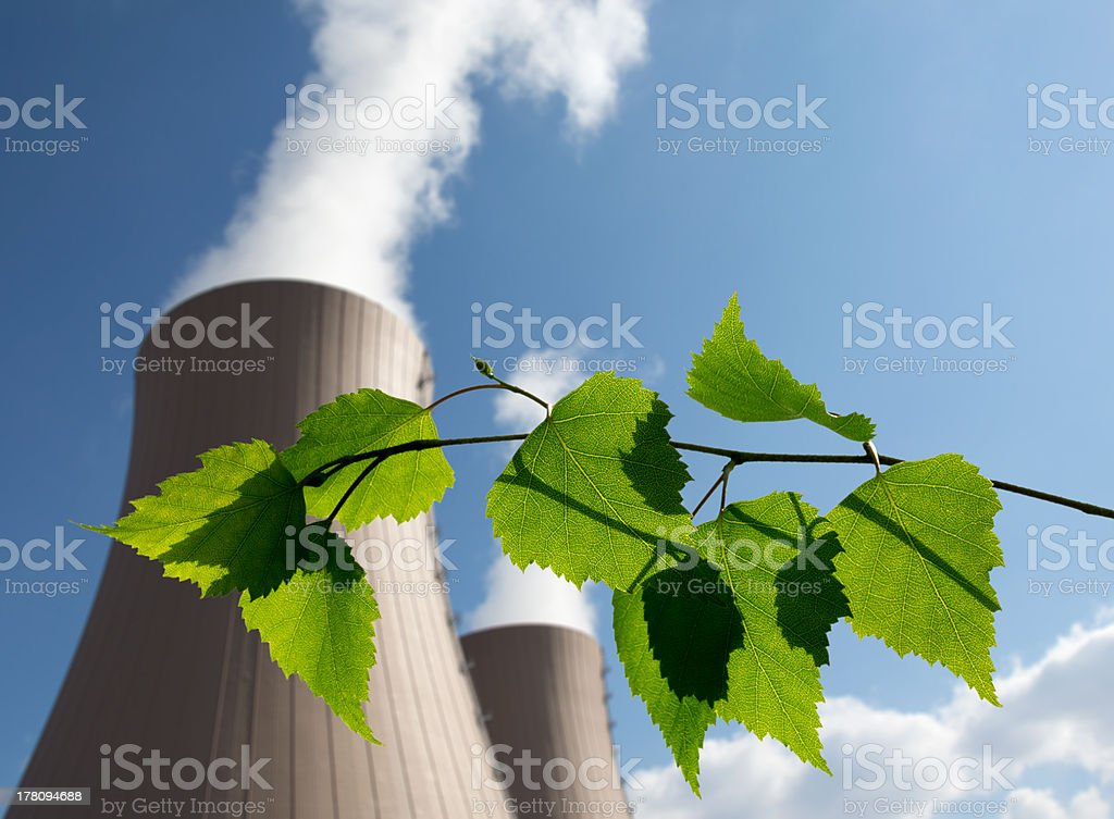 Green branch against nuclear power plant stock photo