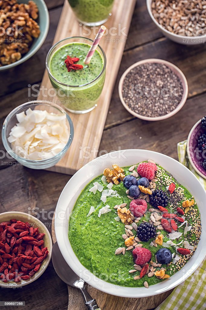 Green Breakfast Smoothie in Bowl with Superfoods on Top stock photo