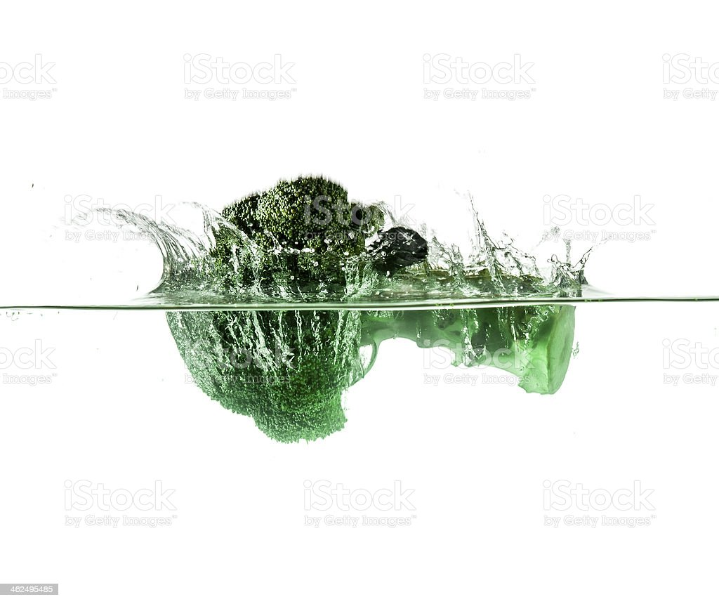 Green broccoli falling in water on white with air bubbles stock photo