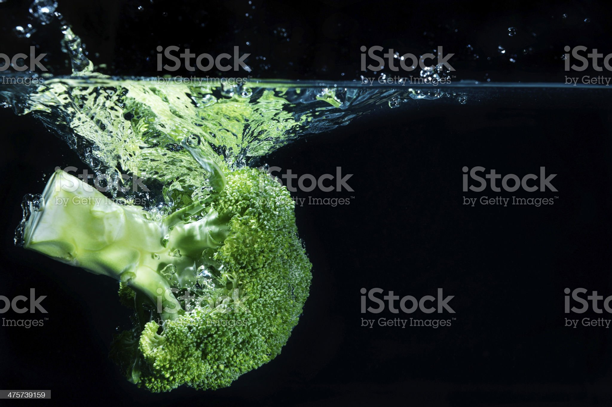 Green broccoli falling in water royalty-free stock photo