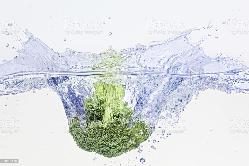 Green broccoli falling in water with air bubbles stock photo