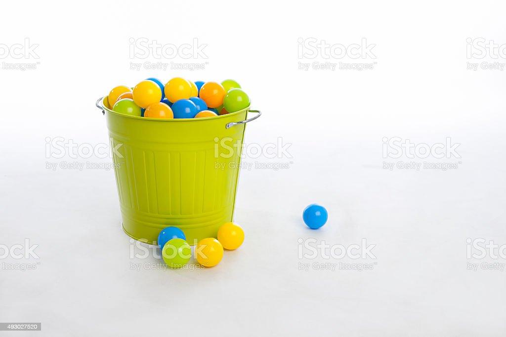 Green Bucket and Plastic Balls Overflowing stock photo