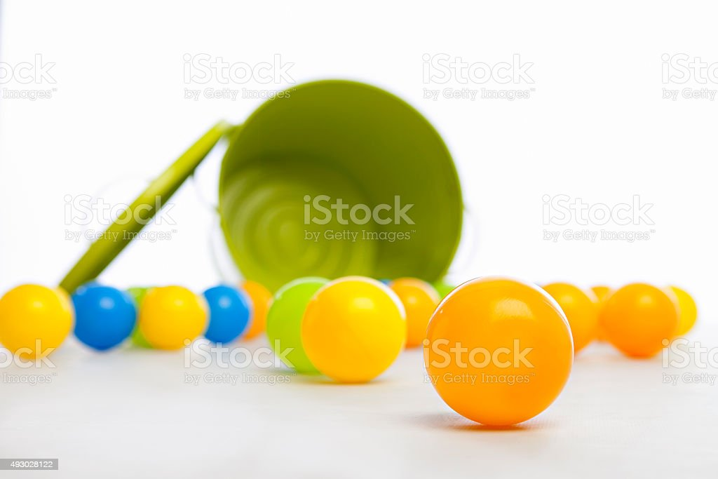 Green Bucket and Plastic Balls spilled stock photo
