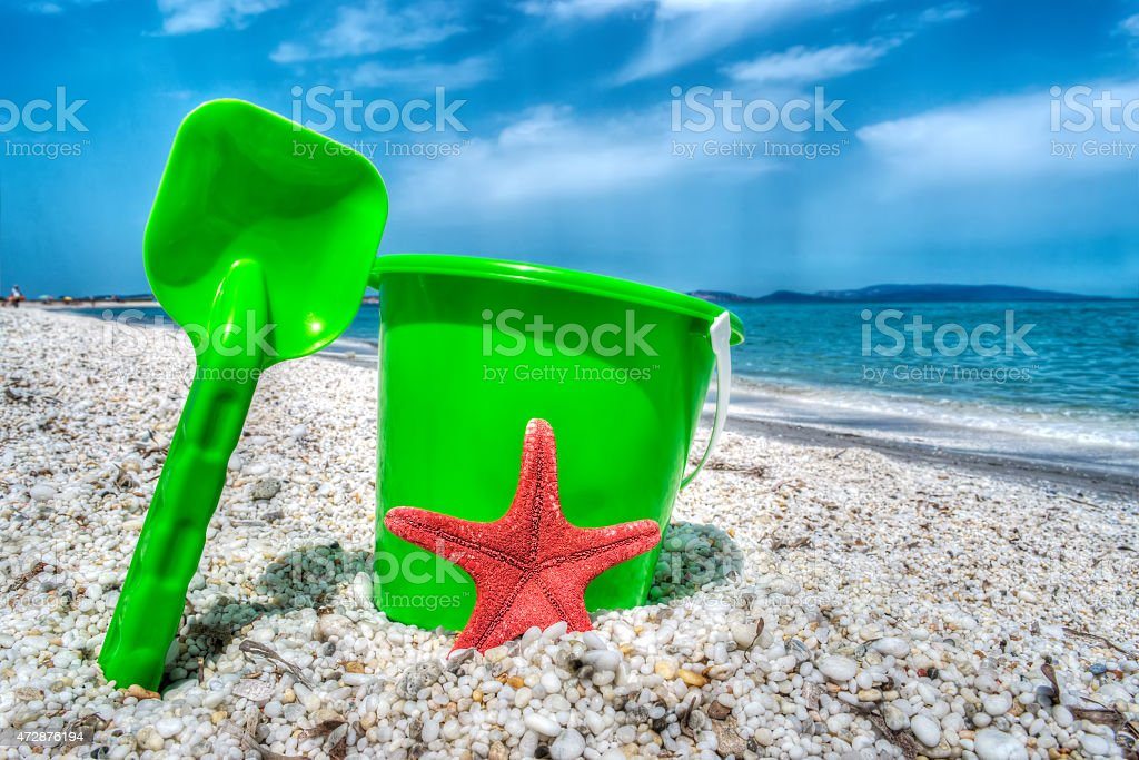 green bucket and spade by the sea in hdr stock photo
