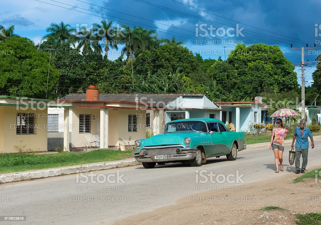 Green Buick drive through the suburb from Santa Clara Cuba stock photo