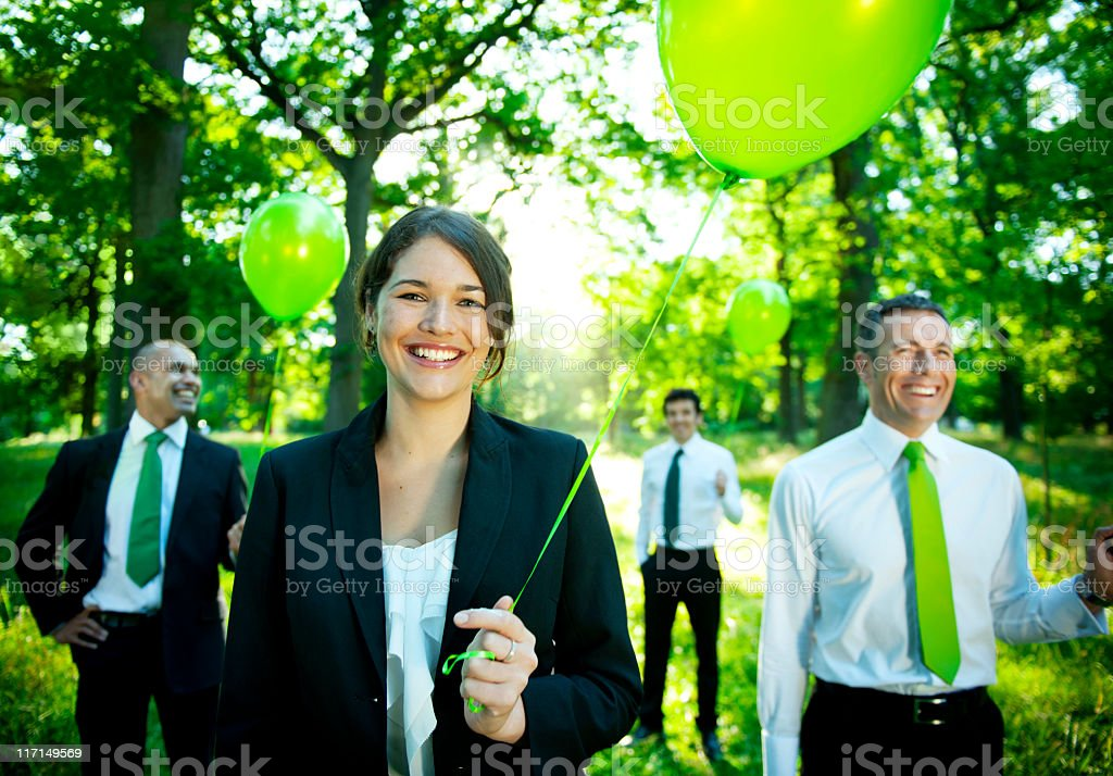 Green Business team standing outdoors holding balloons stock photo