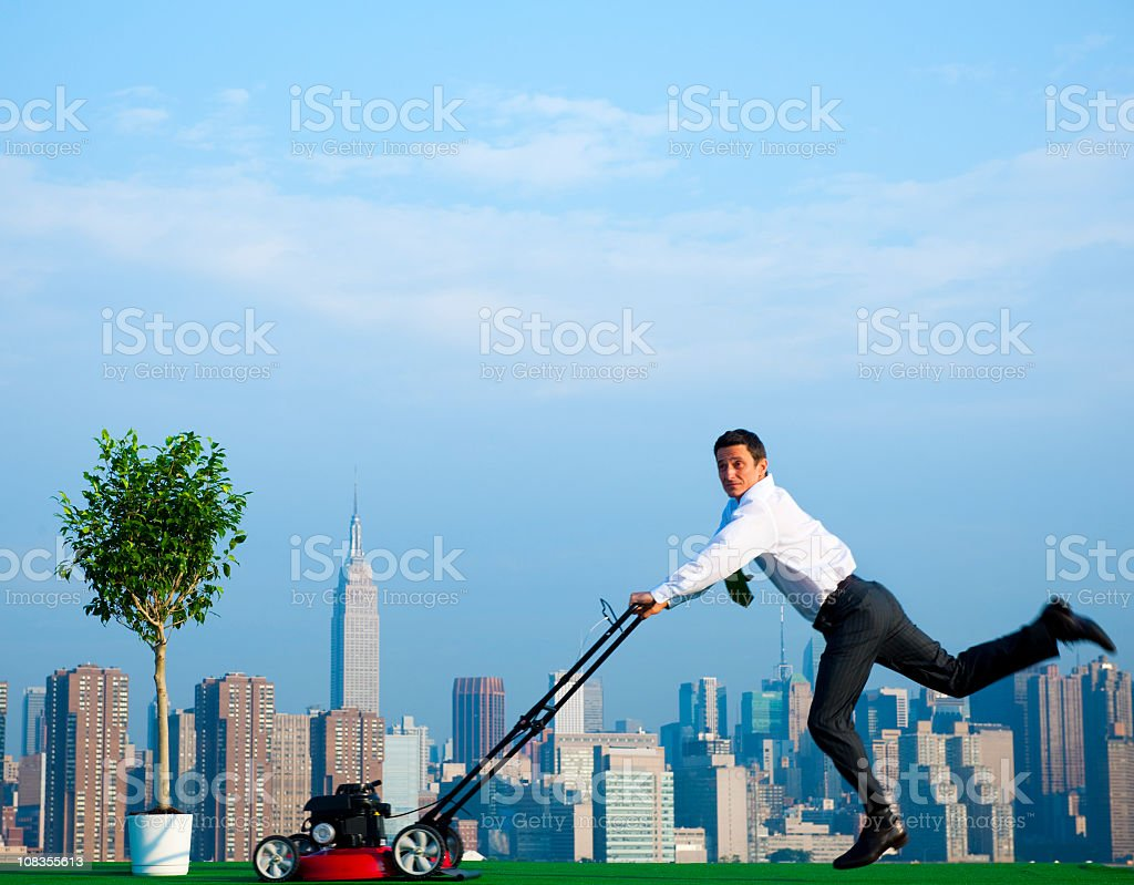 Green Businessman in the City mowing lawn. royalty-free stock photo