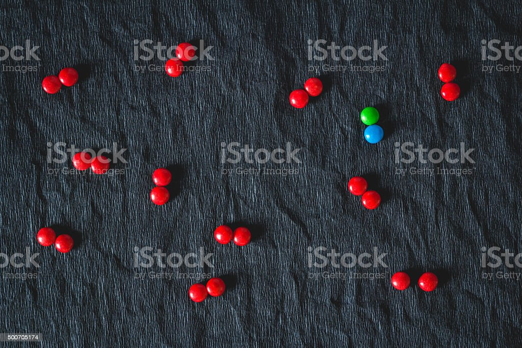 green candy surrounded by red candies stock photo