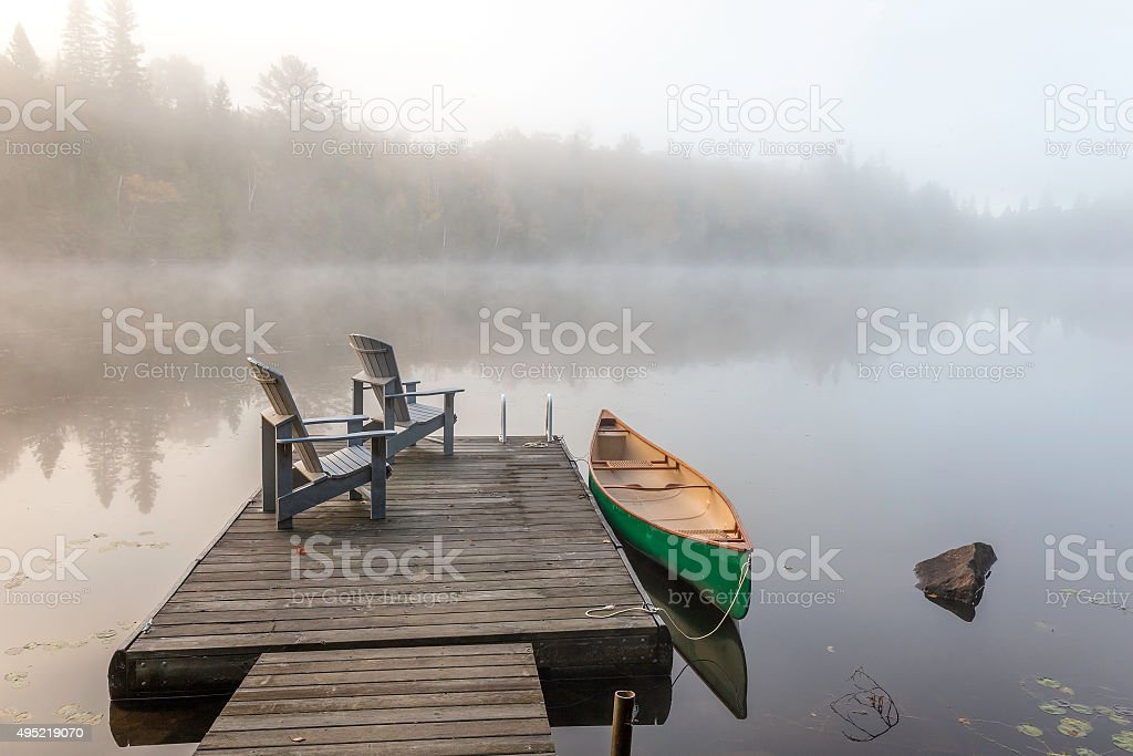 Green Canoe and Dock on a Misty Morning stock photo