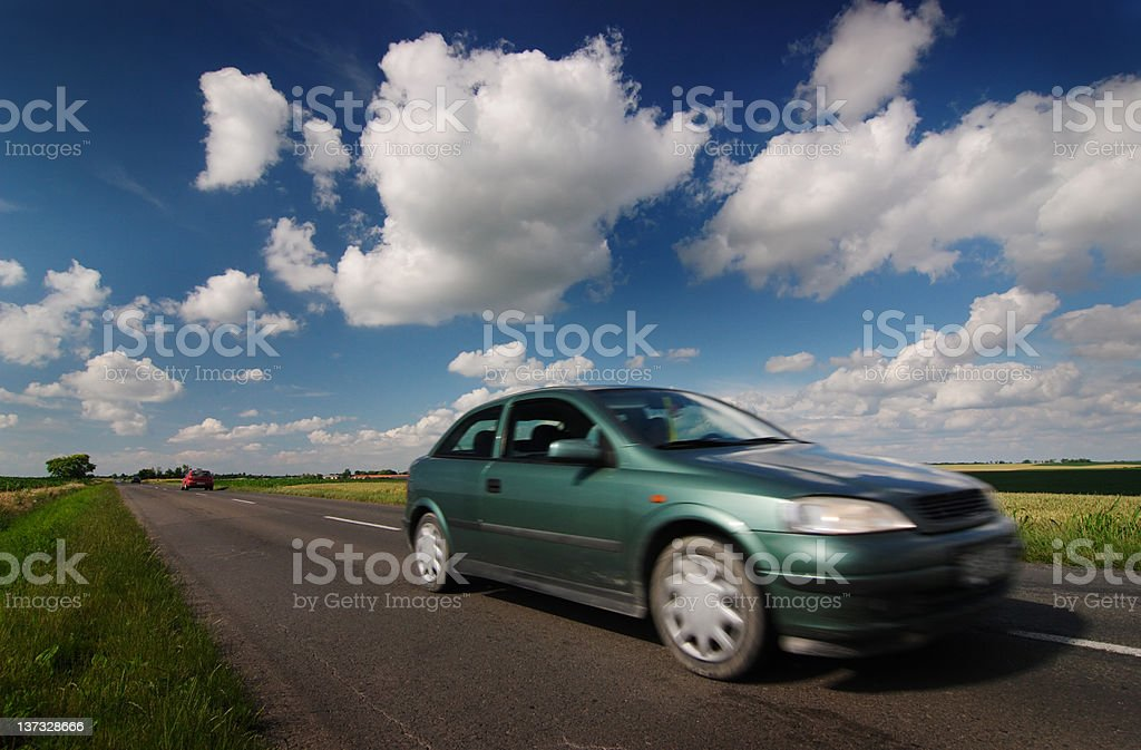 Green car with blue cloudy sky royalty-free stock photo