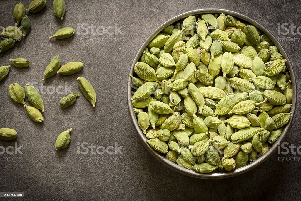 green cardamom pods in  steel bowl stock photo