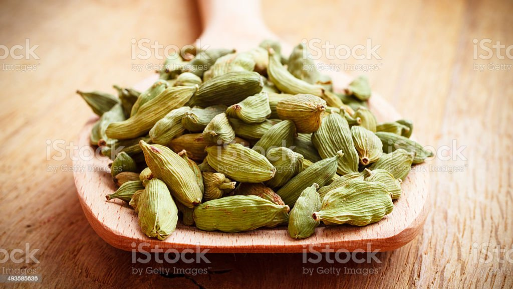 Green cardamom pods on wooden spoon stock photo