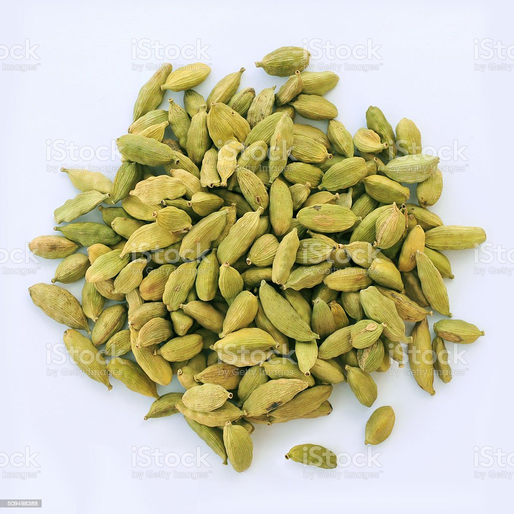 Green cardamom raw spice seeds on the white background. stock photo