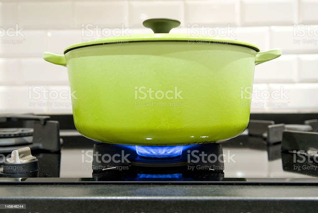 green cast iron cooking pot on a gas stove stock photo