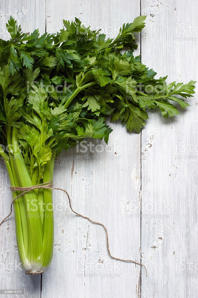 Green celery on the white wooden table stock photo
